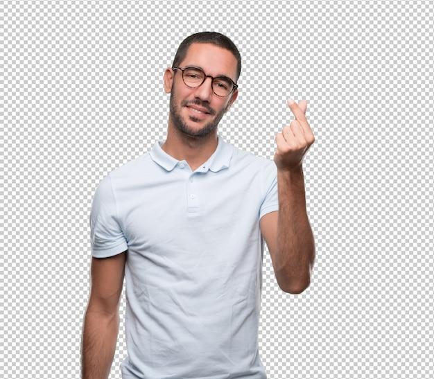 Glücklicher junger mann mit einer geste des haltens von etwas mit seinen fingern Premium PSD
