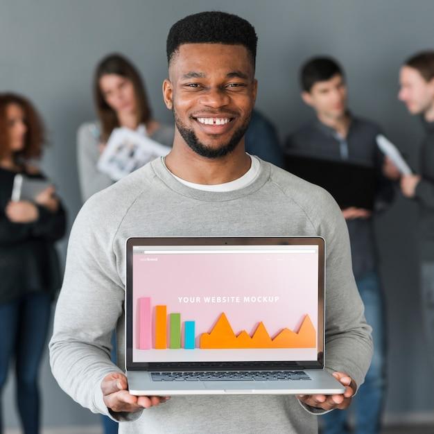Gruppe von personen, die laptopmodell für nächstenliebe hält Kostenlosen PSD