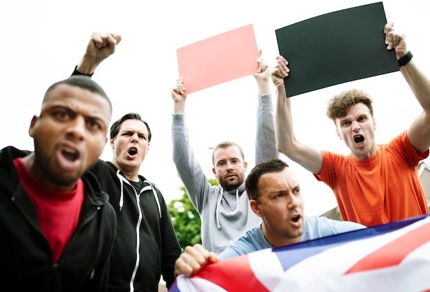 Gruppe wütende männer, die eine britische flagge und leere bretter während eines protests schreien zeigen Premium PSD