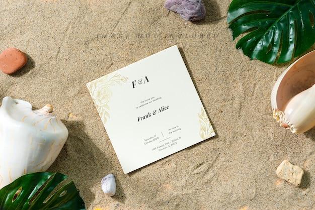 Grußmodellkarte auf einem sandstrand mit muscheln und blättern. Premium PSD