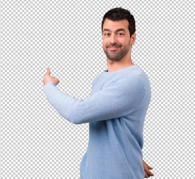 Gut aussehender mann, der zurück mit dem zeigefinger zeigt Premium PSD