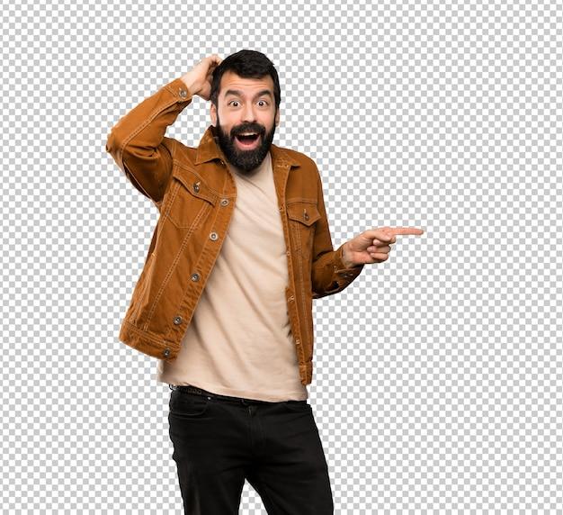 Gut aussehender mann mit bart überrascht und finger auf die seite zeigen Premium PSD
