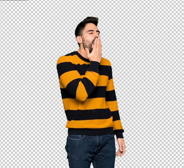 Gut aussehender mann mit der gestreiften strickjacke, die weit offenen mund mit der hand gähnt und bedeckt Premium PSD