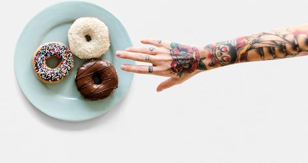 Hand mit tätowierung, die für donut erreicht Premium PSD