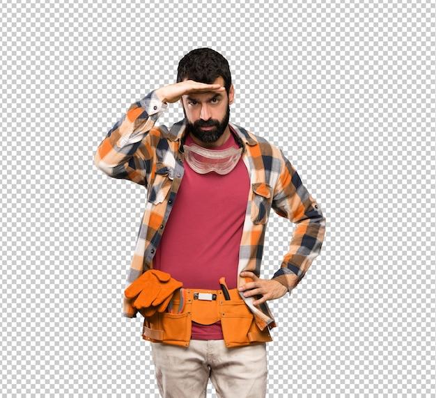 Handwerkermann, der weit weg mit der hand schaut, um etwas zu schauen Premium PSD