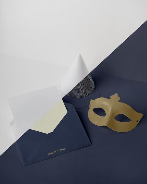 Hoher winkel der karnevalseinladung im umschlag mit kegel und maske Kostenlosen PSD