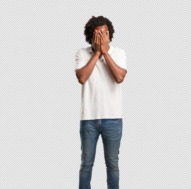 Hübscher afroamerikaner fühlt sich besorgt und erschrocken und schaut und bedeckt gesicht, konzept von furcht und angst Premium PSD