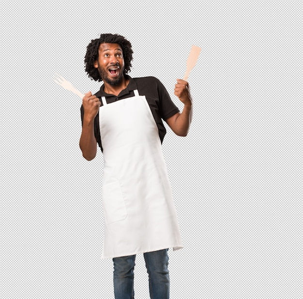 Hübscher afroamerikanerbäcker, der glücklich, überrascht durch ein angebot oder eine förderung, klaffend, springend und stolz schreit Premium PSD