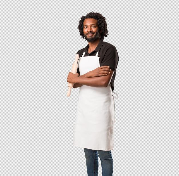Hübscher afroamerikanerbäcker, der seine arme kreuzt, lächelt und glücklich ist, überzeugt und freundlich Premium PSD