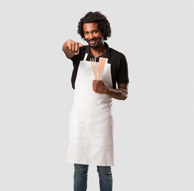 Hübscher afroamerikanerbäcker nett und lächelnd, zeigend auf die front Premium PSD