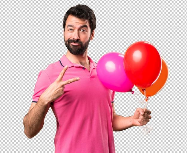Hübscher junger mann, der ballone hält und sieggeste macht Premium PSD