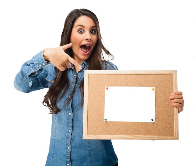 Joyful teenager deutete auf einen kork-board mit einem leeren papier Kostenlosen PSD