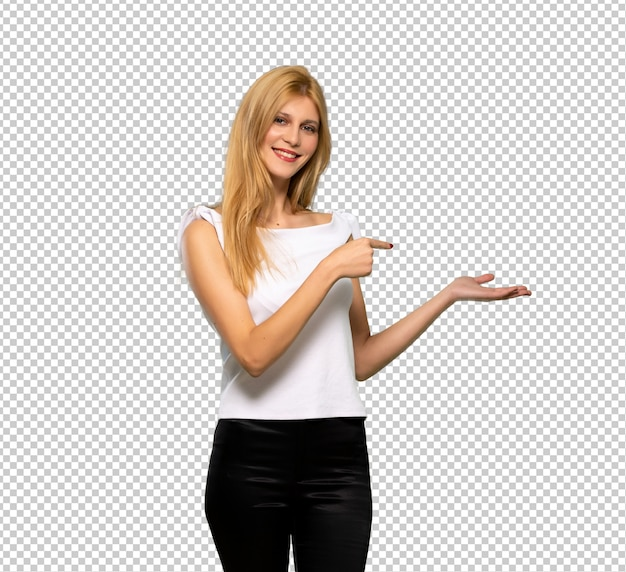 Junge blonde frau, die copyspace imaginär auf der palme hält, um eine anzeige einzufügen Premium PSD