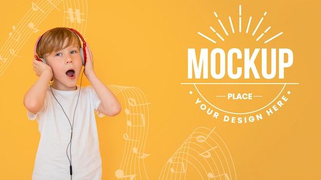 Junge, der musik durch kopfhörer mit hintergrundmodell hört Kostenlosen PSD