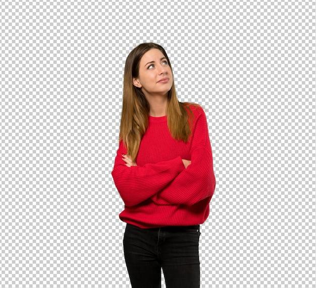 Junge frau mit der roten strickjacke, die oben beim lächeln schaut Premium PSD