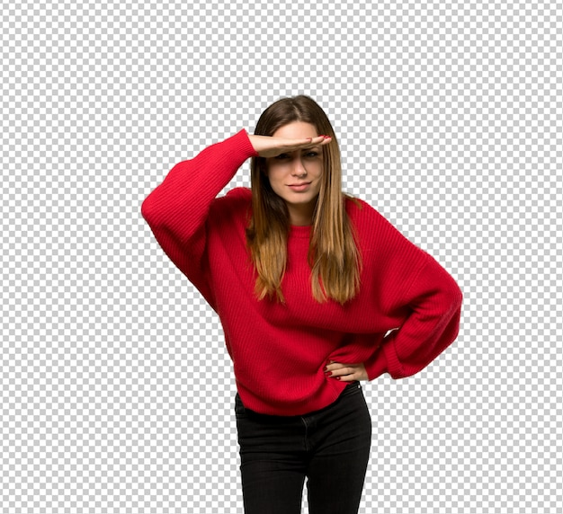 Junge frau mit der roten strickjacke, die weit mit der hand schaut, um etwas zu schauen Premium PSD