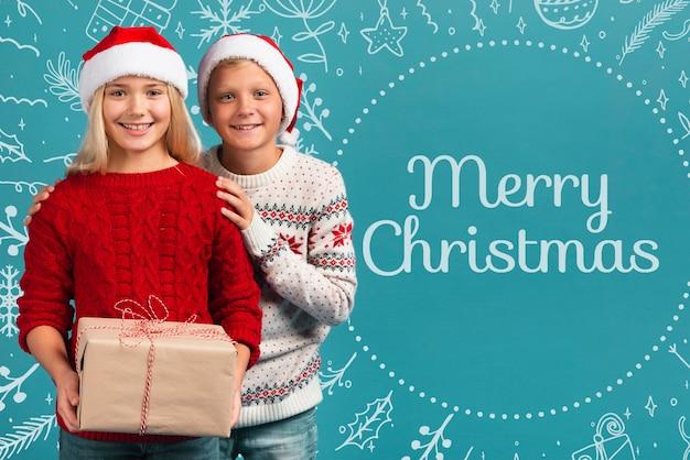 Junge geschwister, die geschenk für weihnachten halten Kostenlosen PSD
