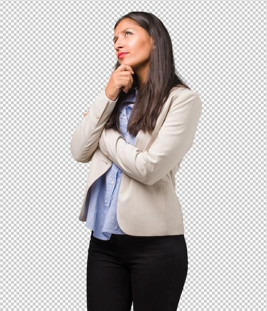 Junge indische geschäftsfrau zweifelnd und verwirrt, an eine idee denkend oder um etwas gesorgt Premium PSD