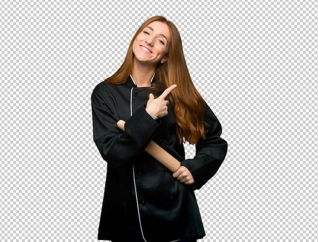 Junge rothaarigecheffrau, die auf die seite zeigt, um ein produkt darzustellen Premium PSD