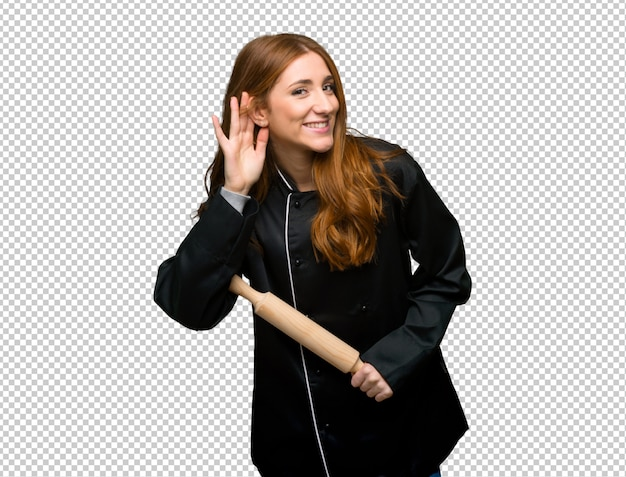 Junge rothaarigecheffrau, die auf etwas hört, indem sie hand auf das ohr setzt Premium PSD