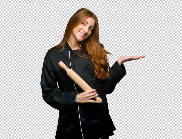 Junge rothaarigecheffrau, die eine idee beim schauen lächelnd in richtung darstellt Premium PSD