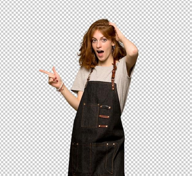 Junge rothaarigefrau mit schutzblech finger auf die seite zeigend und ein produkt darstellend Premium PSD