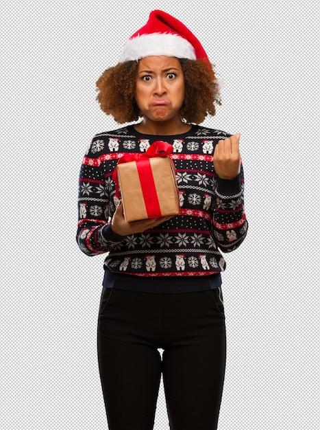 Junge schwarze frau, die ein geschenk am weihnachtstag eine geste des bedarfs tuend anhält Premium PSD