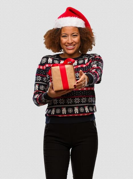 Junge schwarze frau, die ein geschenk am weihnachtstag hält, um heraus jemanden zu grüßen Premium PSD