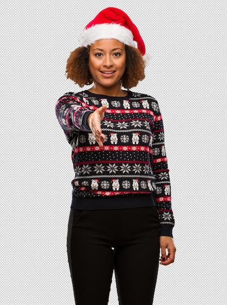Junge schwarze frau in einer modischen weihnachtsstrickjacke mit dem druck, der heraus erreicht, um jemand zu grüßen Premium PSD