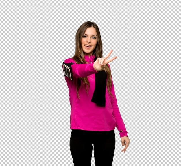 Junge sportfrau, die siegeszeichen lächelt und zeigt Premium PSD