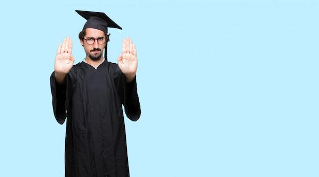 Junger abgestufter mann signalstopp mit beiden handflächen nach vorne gerichtet Premium PSD