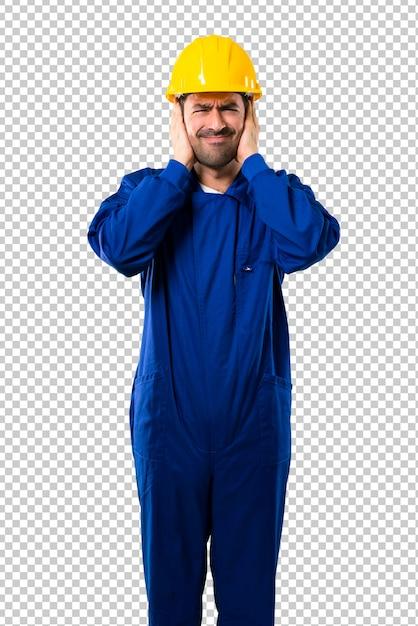 Junger arbeiter mit dem sturzhelm, der beide ohren mit den händen bedeckt. frustrierter ausdruck Premium PSD