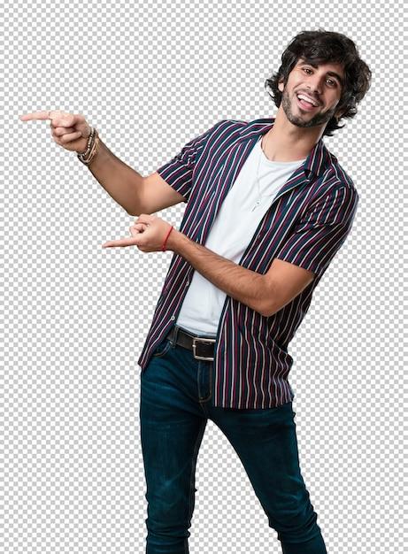 Junger gutaussehender mann, der auf die seite, das lächeln überrascht zeigt, etwas darstellend, natürlich und zufällig Premium PSD