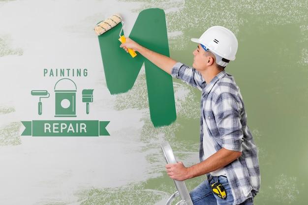 Junger handwerker, der die wand in grün malt Kostenlosen PSD