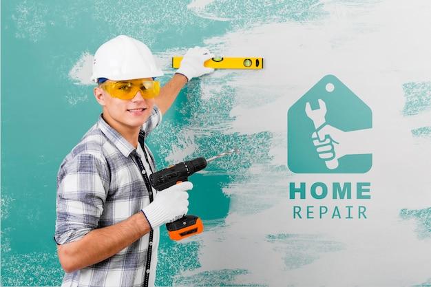 Junger handwerker, der einen bohrer hält Kostenlosen PSD