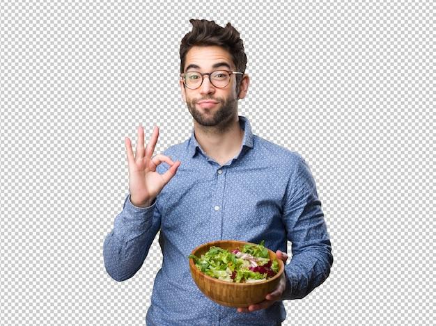 Junger mann, der einen salat tut, der okaygeste tut Premium PSD