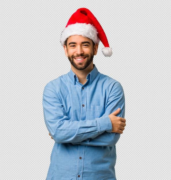 Junger mann, der sankt-hutüberfahrtarme trägt, lächelt und entspannt Premium PSD
