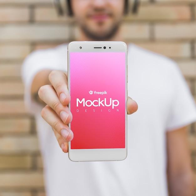Junger mann mit einem smartphonemodell Kostenlosen PSD