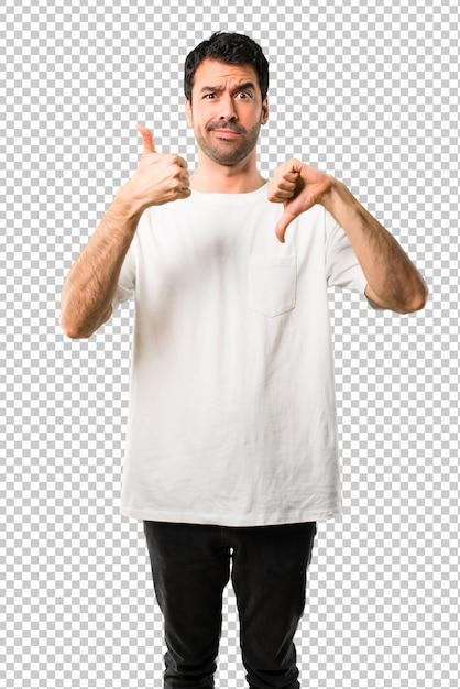 Junger mann mit weißem hemd, das gut-schlechtes zeichen macht. unentschlossene person zwischen ja oder nein Premium PSD