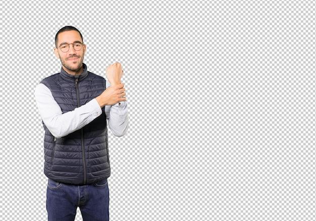 Junger mann zeigt auf sein handgelenk Premium PSD