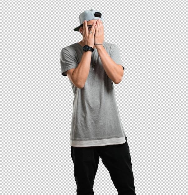 Junger rappermann fühlt sich besorgt und erschrocken und schaut und bedeckt gesicht, konzept der furcht und der angst Premium PSD