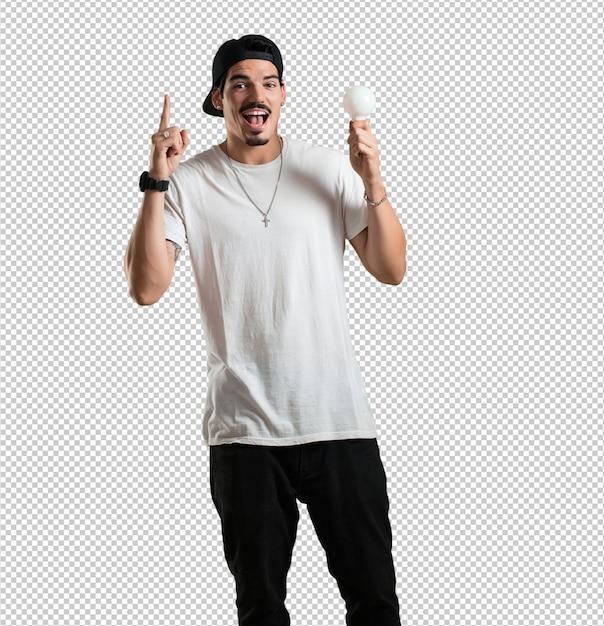 Junger rappermann nett und aufgeregt, aufwärts zeigend und halten eine glühlampe als symbol der idee, der fantasie, der geistesflüssigkeit und der klugheit, inspirierend foto Premium PSD