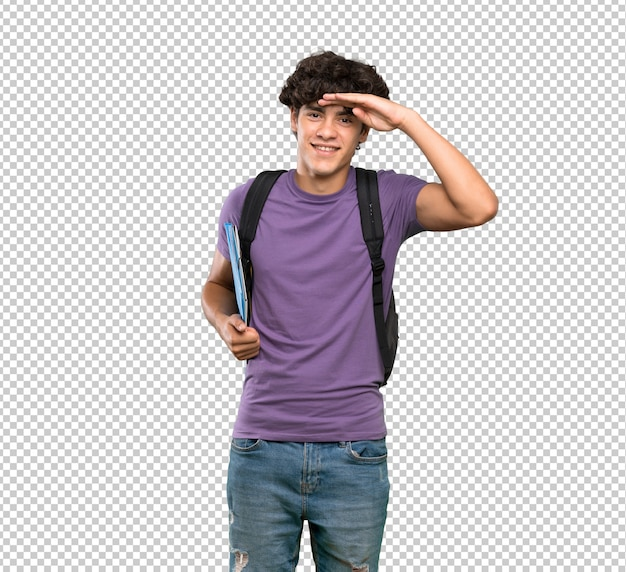 Junger studentenmann, der weit weg mit der hand schaut, um etwas zu schauen Premium PSD