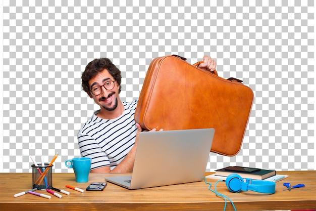 Junger verrückter grafikdesigner auf einem schreibtisch mit einem laptop und mit einem lederkoffergepäck Premium PSD