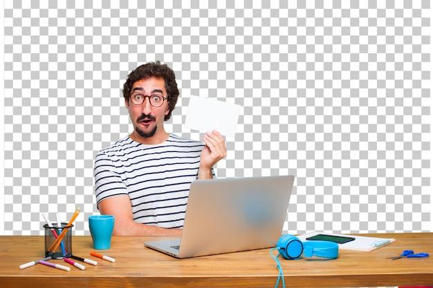 Junger verrückter grafikdesigner auf einem schreibtisch mit einem laptop und mit einem plakat Premium PSD
