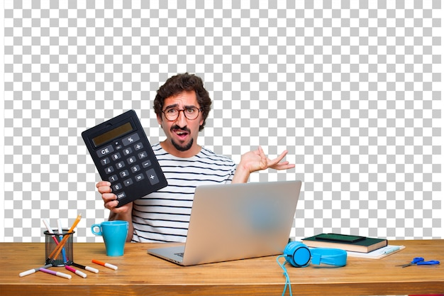 Junger verrückter grafikdesigner auf einem schreibtisch mit einem laptop und mit einem taschenrechner Premium PSD
