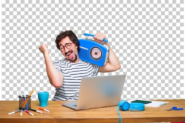 Junger verrückter grafikdesigner auf einem schreibtisch mit einem laptop und mit einem weinleseradio Premium PSD