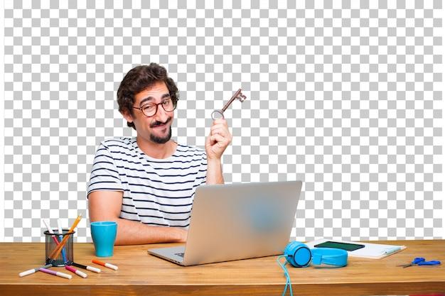 Junger verrückter grafikdesigner auf einem schreibtisch mit einem laptop und mit einem weinleseschlüssel Premium PSD