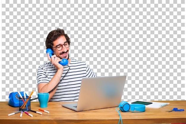 Junger verrückter grafikdesigner auf einem schreibtisch mit einem laptop und mit einem weinlesetelefon Premium PSD