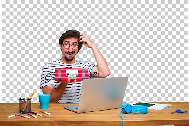 Junger verrückter grafikdesigner auf einem schreibtisch mit einem laptop und mit einer dynamitbombe Premium PSD